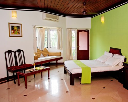 A well furnished bedroom with living area and outside view.