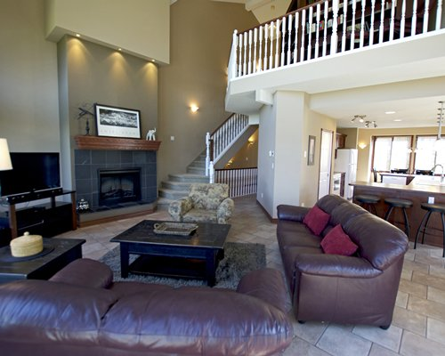 Living room with an open plan kitchen breakfast bar fireplace and stairway leading to an indoor balcony.