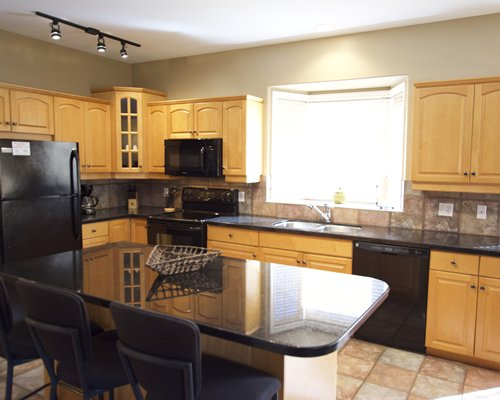 A well equipped kitchen with breakfast bar and microwave.