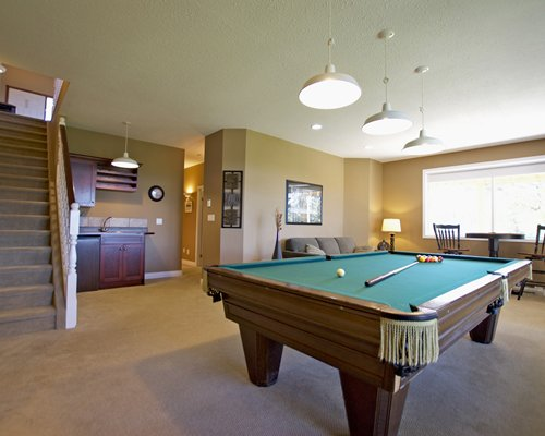 Indoor recreation room with pool table lounge area and a stairway.