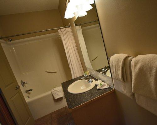 A bathroom with bathtub shower and a single sink vanity.