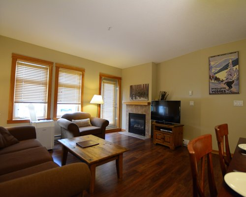 A well furnished living room with a television fireplace dining area and outside view.