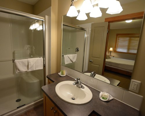 A bathroom with a shower stall closed sink vanity and view of the bedroom.