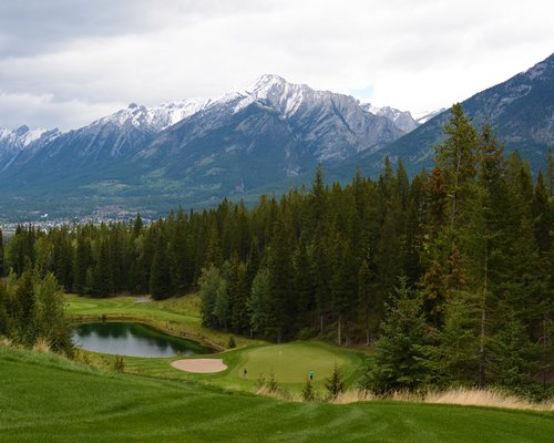 Golf course with the waterfront alongside the wooded area and mountains.