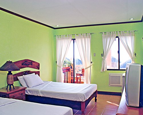 A well furnished bedroom with two twin beds television and balcony.