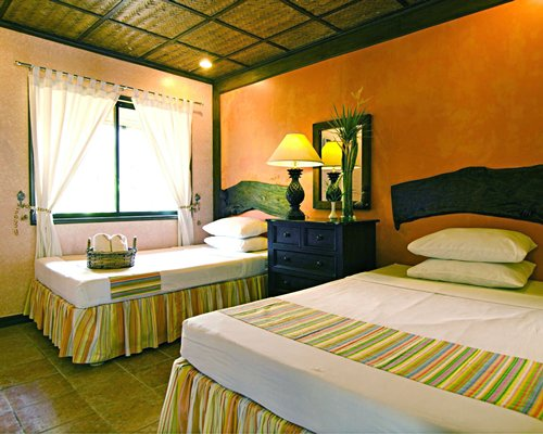 A well furnished bedroom with two twin beds and outside view.