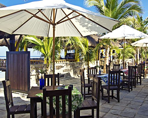 An outdoor restaurant with patio tables and sunshades surrounded by trees.