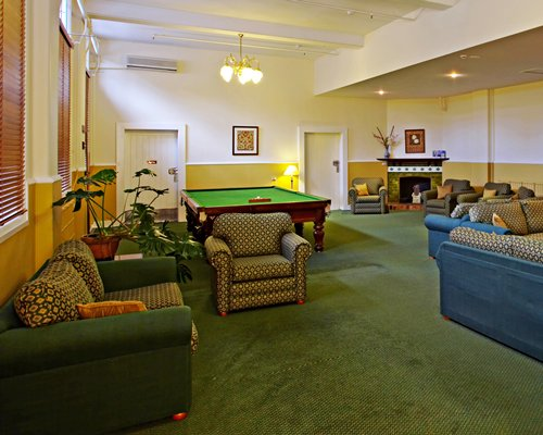An indoor recreational room with a fireplace and pool table.
