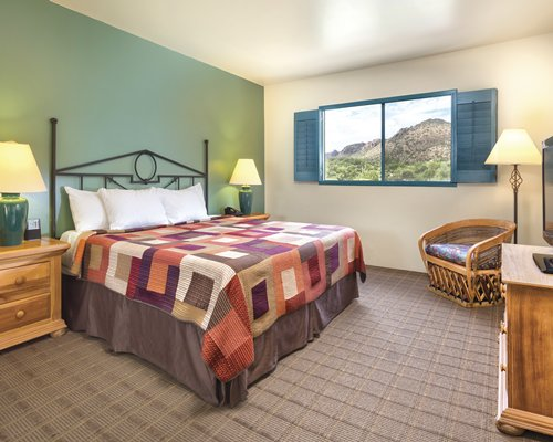 A well furnished bedroom with a television and the mountain view.