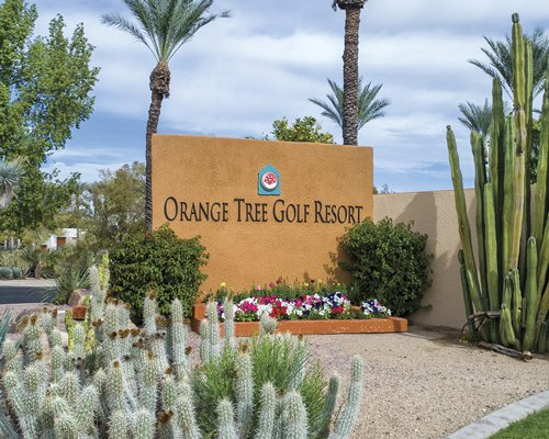 An exterior view of the Orange Tree Golf Resort with flowering shrubs.