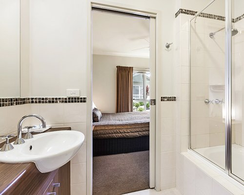A bathroom with shower and single sink vanity alongside bedroom.