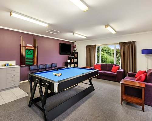 A well furnished living room with a television bookshelf and pool table.