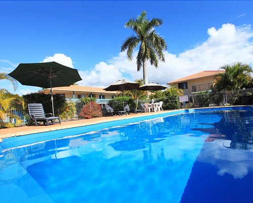 Large outdoor swimming pool with sunshades dining and chaise lounge chairs.