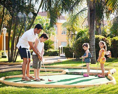 A man playing golf with kids alongside resort units.