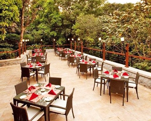 An outdoor fine dining restaurant surrounded by trees.