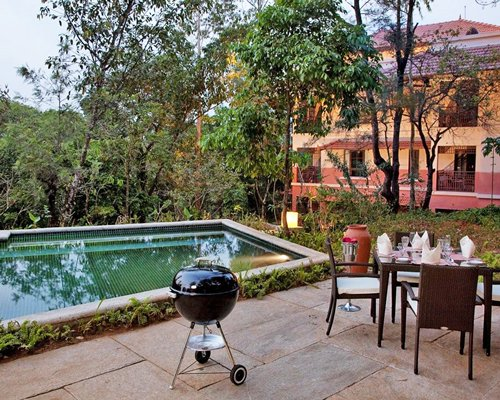 An outdoor pool with dining table and a barbeque grill alongside multi story resort units.