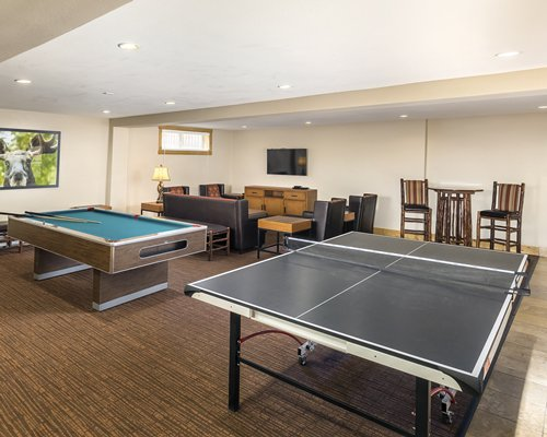 An indoor recreation room with pool and ping pong table and a television.