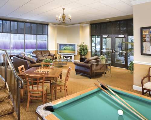 An indoor recreational area with pool table chess board and television.