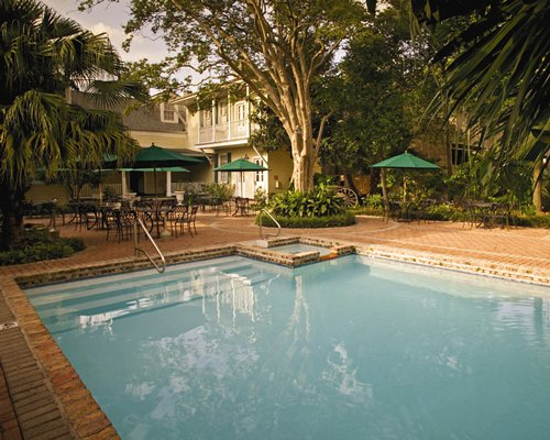 An outdoor swimming pool with hot tub and dining area alongside multi story resort units.