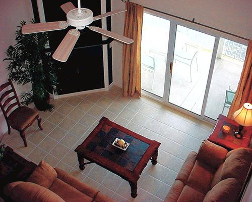 A well furnished living room with fan and outdoor patio with patio chairs.