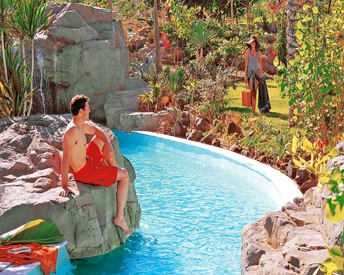 A man at a grotto pool and woman at a landscaped area.
