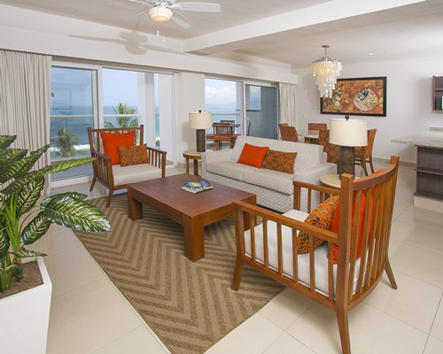 A well furnished living room with dining area balcony and ocean view.