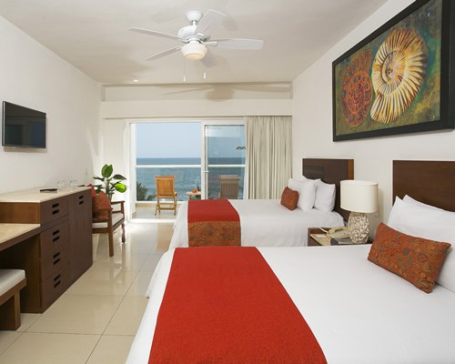 A well furnished bedroom with two king beds television balcony with patio chairs and ocean view.