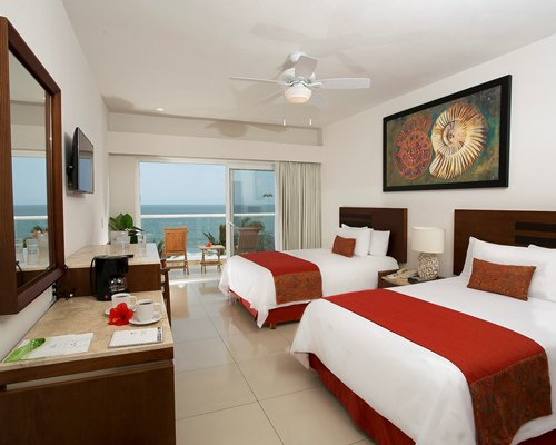 A well furnished bedroom with two king beds television balcony with patio chairs and water view.
