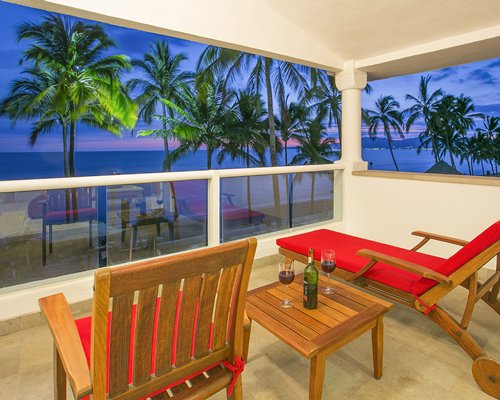 A balcony with patio furniture chaise lounge chairs and the beach view.