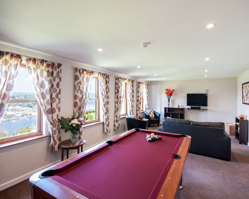 A well furnished living room with a television pool table and outside view.