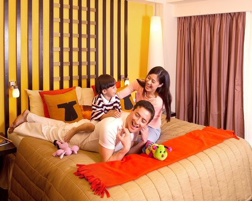 A family at well furnished bedroom with queen bed.