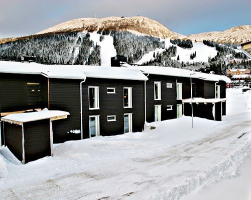 Exterior view of a unit covered with snow alongside mountains.