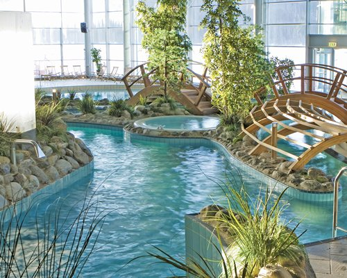 A bridge over an indoor swimming pool with hot tub and an outside view.