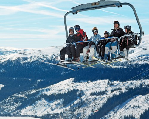 View of people on the chairlift above the wooded area during winter.