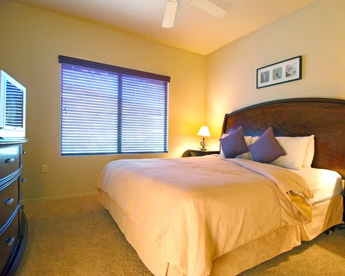 A well furnished bedroom with king bed and an outside view.