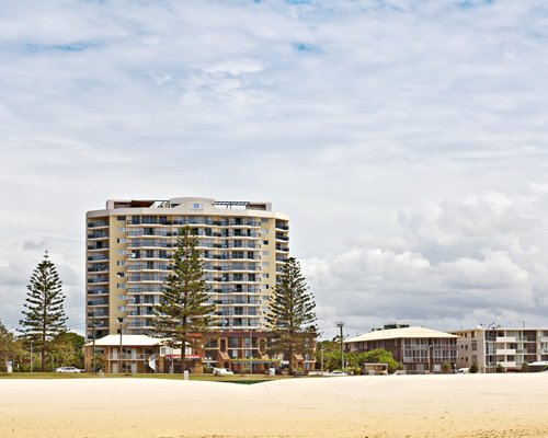 Exterior view of Wyndham Kirra Beach resort with trees.