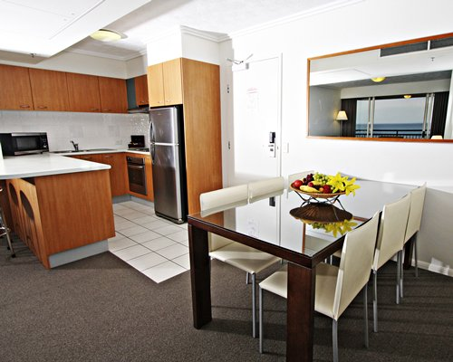 An open plan kitchen with breakfast bar and wooden dining area.