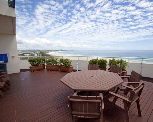 A balcony with a patio furniture alongside the ocean.