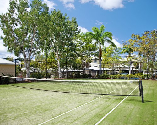 An outdoor tennis court with trees alongside resort units.