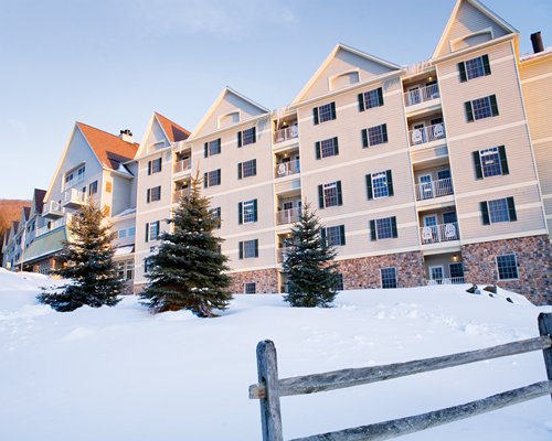 An exterior view of multi story resort units with pine trees covered in snow.