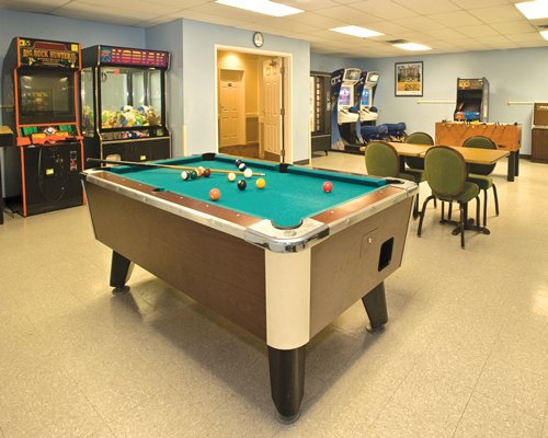 A recreational room with pool table and arcade games.