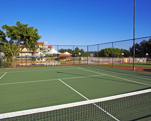 An outdoor tennis court with trees alongside the swimming pool.