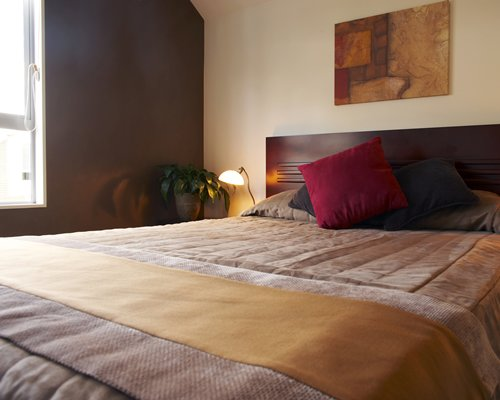 A well furnished bedroom with a queen bed and outside view.