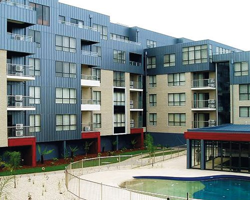 Exterior view of multi story units and outdoor swimming pool.