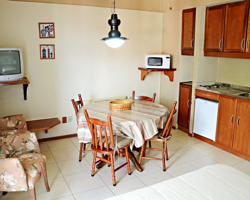 A well furnished open plan living kitchen and dining area with a television.
