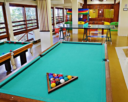 An indoor recreation room with pool table and ping pong.