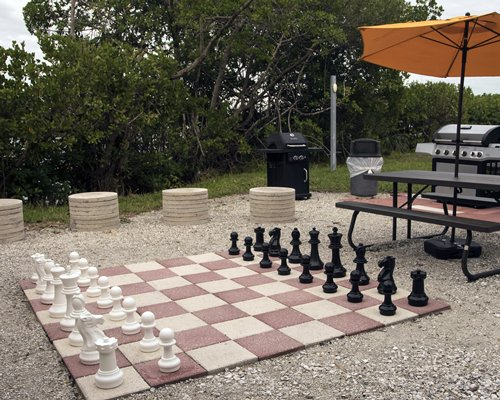 An outdoor picnic area with barbecue grills and a giant chess set up.