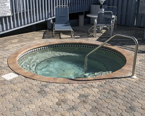 An outdoor hot tub with chiase lounge chairs.