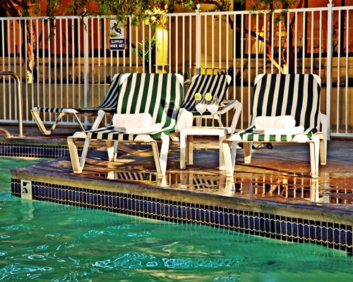 Outdoor swimming pool with chaise lounge chairs and beverages.