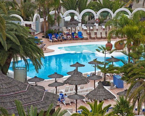 Outdoor swimming pool with chaise lounge chairs thatched sunshades and palm trees.